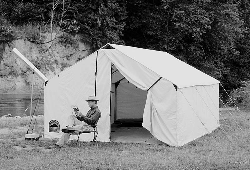 Black and white photo of man in hat sitting by Wall Tent next to river. tent stove pipe poking out of tent