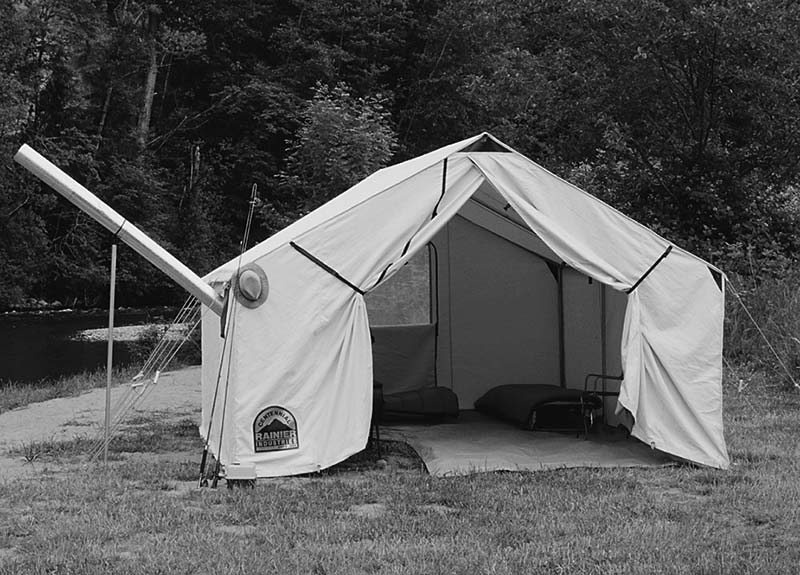 Black and white photo of Wall Tent next to river. Tent fly open exposing interior. sleeping bags and cots with tent stove pipe