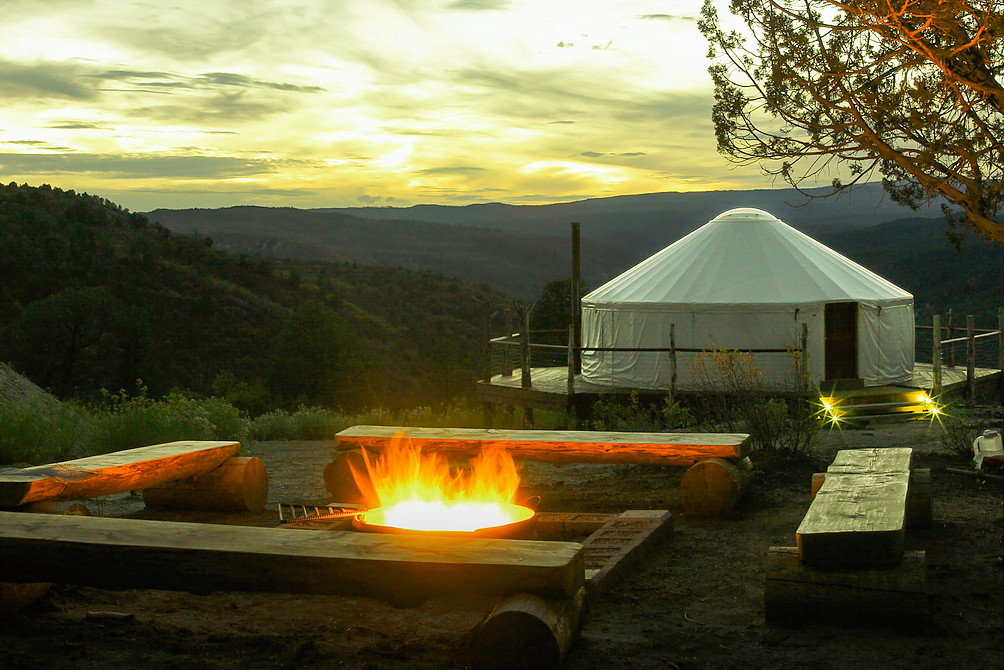 A Rainer Outdoor Yurt in a plush Oregon valley in back of a cheery campfire ring with log benches