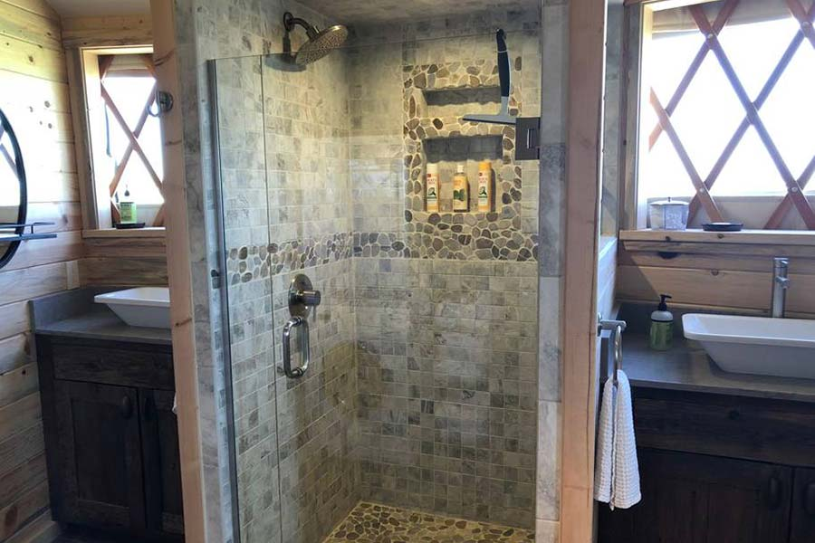 How large can a Yurt bathroom be? Here is a double sink vanity, master bath with walk in tiled shower and 2 windows! This yurt master bathroom design is a great example of the possibilities for your making a fabulous Glamping yurt.