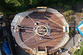 Yurt construction at Rainier Outdoor Yurt Park, Tukwila Wa. Setting up the crown ring and rafters with lattice wall standing with tension wire.