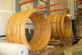Wooden Yurt roof, crown, dome, rings hanging from shelf struts in Rainier Outdoor yurt kit storage manufacturing plant.