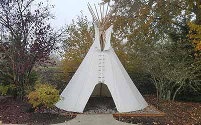 Photo of a Rainier Tipi set up in a light river forest bush camp ground