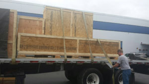 Rainier Shipping Truck with yurt crates on flatbed with man tightening banding straps on truck